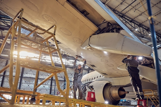 Low angle portrait of engineers working on airplane wing in passenger aircraft maintenance factory
