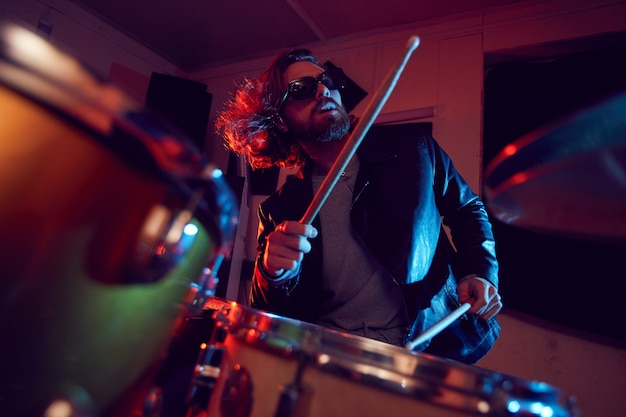 Low angle portrait of handsome young man rocking drums during music concert in bright lights