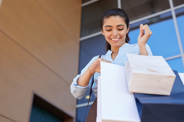 Low angle portrait of happy young woman looking into shopping bag and smiling while leaving mall with purchases, copy space