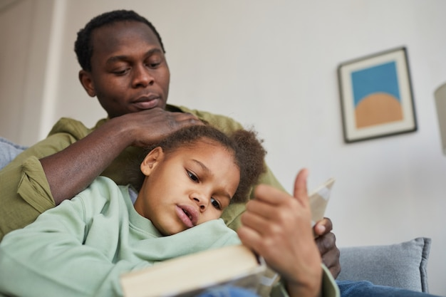 Low angle portrait of loving african-american father and daughter reading while sitting on couch together in cozy home interior, copy space