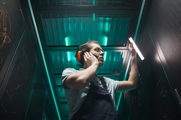 Low angle portrait of male network engineer speaking by smartphone in server room while working in data center, copy space