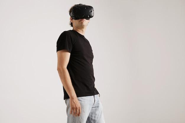 Ritratto di angolo basso di un uomo che indossa la cuffia avricolare di vr, maglietta nera in bianco e jeans che guardano intorno isolati su bianco