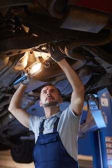 Low angle portrait of mature mechanic looking under car on lift and holding lamp light during inspection in auto repair workshop, copy space