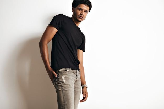 灰色のジーンズと白で隔離のラベルのない黒のtシャツのセクシーな筋肉のアフリカ系アメリカ人の若いモデルのローアングルの肖像画