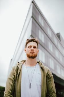 Низкоугольный портрет молодого мужчины в серой футболке с курткой и позирующего на открытом воздухе