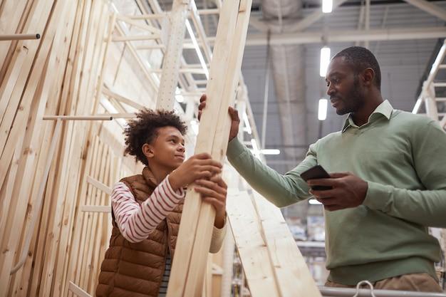 Низкоугольный портрет афро-американского отца и сына, делающих покупки вместе в строительном магазине, фокус на мужчине, выбирающем деревянные доски для строительства или улучшения дома
