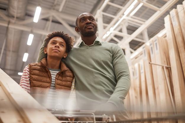 Низкоугольный портрет афро-американского отца и сына, делающих покупки в строительном магазине, толкая тележку с деревянными досками для строительства или улучшения дома