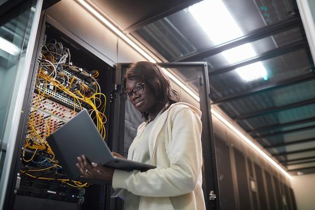 Низкоугольный портрет афроамериканского сетевого инженера, стоящего у серверного шкафа и держащего ноутбук во время работы с суперкомпьютером в центре обработки данных, копировальное пространство