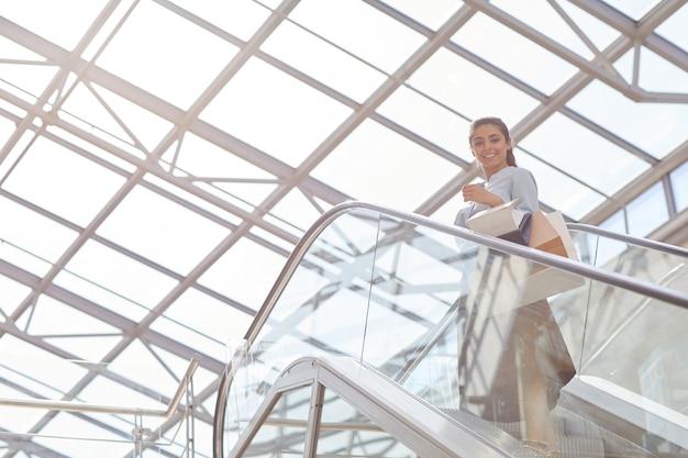 Низкоугольный портрет красивой молодой женщины, стоящей на вершине эскалатора и улыбающейся в камеру под графической стеклянной крышей торгового центра, копией пространства