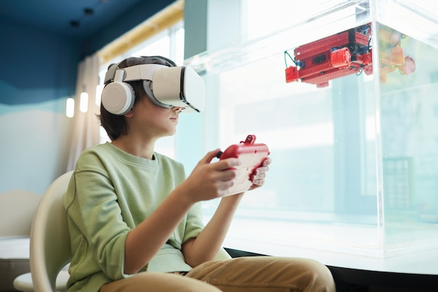 학교 실험실에서 로봇 보트를 작동하는 동안 vr 헤드셋을 착용한 소년의 낮은 각도 초상화, 복사 공간