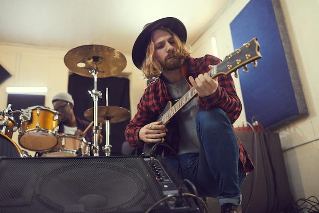 Низкоугольный портрет современного длинноволосого музыканта, настраивающего гитару во время проверки звука