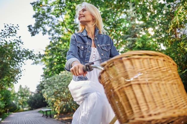 여름 녹색 대로에서 좋은 따뜻한 날씨를 즐기는 데님 재킷과 흰색 드레스를 입은 행복한 미소 성인 여성의 낮은 각도 초상화