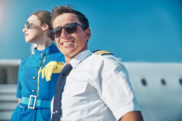 태양 아래 스튜어디스와 함께 비행기 근처에 서 있는 선글라스를 쓴 유쾌한 잘생긴 남자의 낮은 각도 초상화