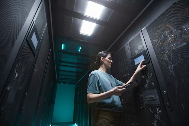 Низкоугольный портрет военной женщины, использующей панель управления при настройке серверов в центре обработки данных, копировальное пространство