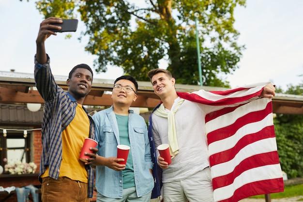 Низкоугольный портрет многонациональной группы, делающей селфи, наслаждаясь вечеринкой на открытом воздухе летом в день независимости