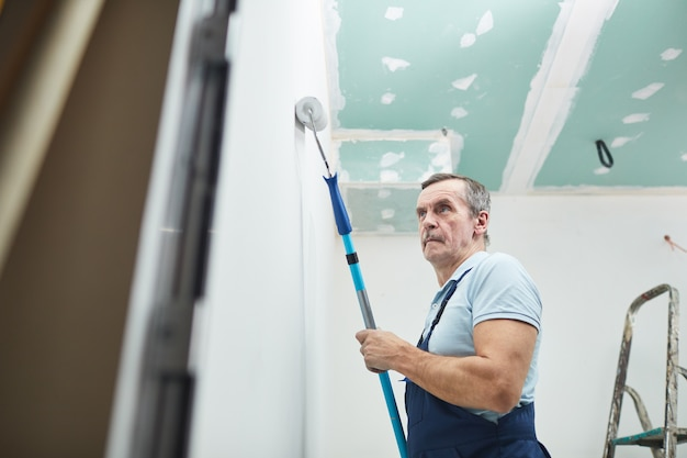Низкоугольный портрет старшего строителя, расписывающего стену во время ремонта дома, копия пространства