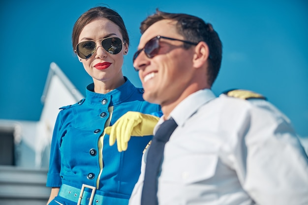 비행 후 야외에서 휴식을 취하는 동안 남자에게 기대어 웃고 있는 아름다운 젊은 여성의 낮은 각도 초상화