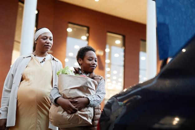 Низкоугольный портрет афроамериканского мальчика-подростка, несущего продукты в машину, помогая маме делать покупки, скопируйте пространство