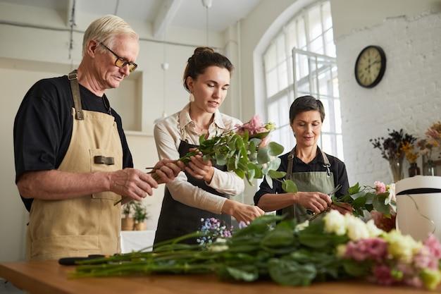 Низкоугольный портрет трех креативных флористов, создающих цветочные композиции в мастерской
