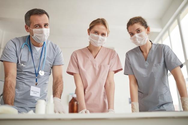 Низкоугольный портрет трех врачей в масках, смотрящих в камеру, стоя у стола в медицинской клинике