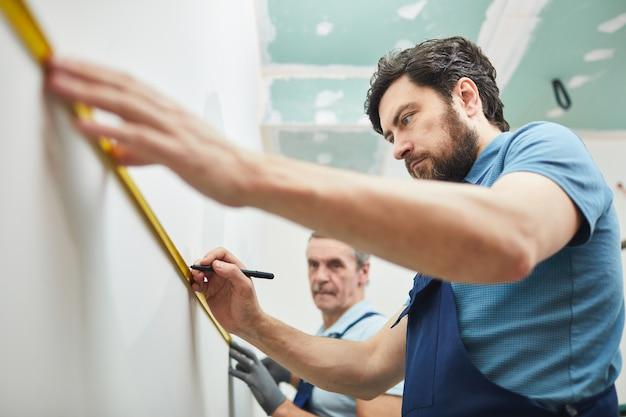 Низкоугольный портрет двух рабочих-строителей, измеряющих стену во время ремонта дома, копия пространства