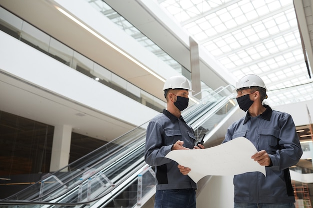 마스크를 착용하고 쇼핑몰이나 사무실 건물에 서있는 동안 계획을 논의하는 두 명의 건설 노동자의 낮은 각도 초상화,