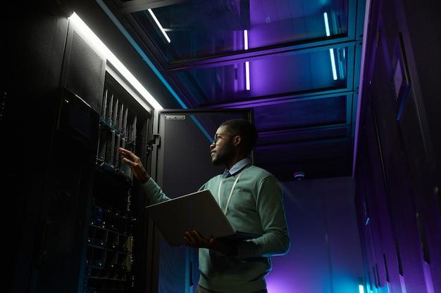 Низкоугольный портрет молодого афроамериканского инженера по обработке данных, работающего с суперкомпьютером в серверной комнате, освещенного синим светом и держащего ноутбук, копировальное пространство