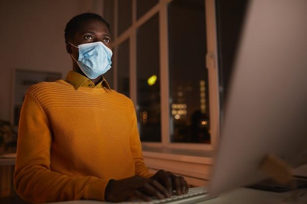 暗い、コピースペースで画面に照らされたコンピューターを使用しながらオフィスでマスクを身に着けている若いアフリカ系アメリカ人男性のローアングルの肖像画