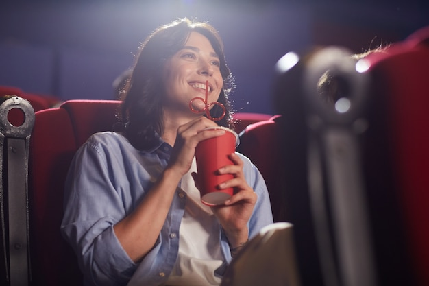 Low angle portrait of smiling young woman in cinema watching movie alone and drinking soda, looking up at screen, copy space