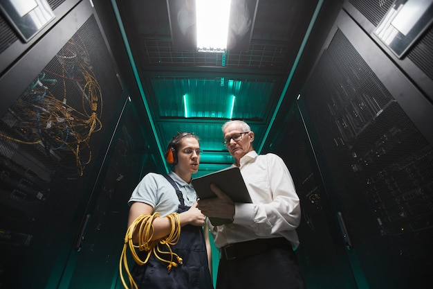 Low angle portrait of two engineers using tablet in server room while doing maintenance work in data center, copy space