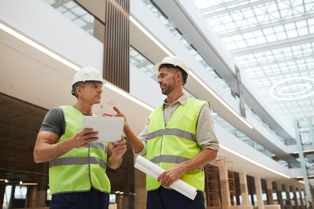 Low angle portrait of two professional building contractors using digital tablet while standing at construction site in office building,