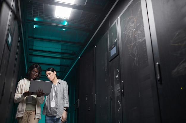 Low angle portrait of two young women using laptop in server room while setting up supercomputer network, copy space