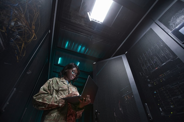 Low angle portrait of young african-american woman wearing military uniform using laptop while standing in server room, copy space