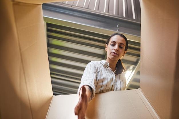 자기 저장 장치를로드하는 동안 상자에 도달하는 젊은 여성의 낮은 각도 pov 샷, 복사 공간