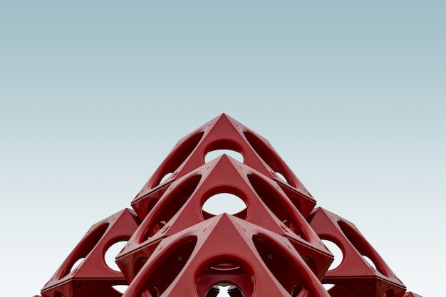 Low angle of a red geometrical structure under the blue sky