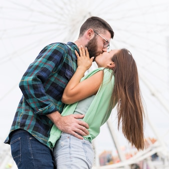 Low angle of romantic couple kissing outdoors