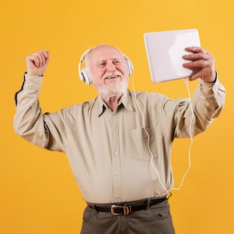 Low angle senior dancing and listening music