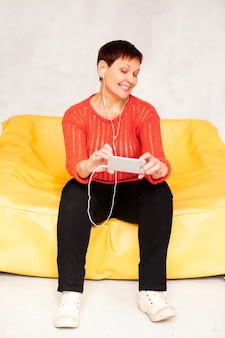Low angle senior female on couch listening music