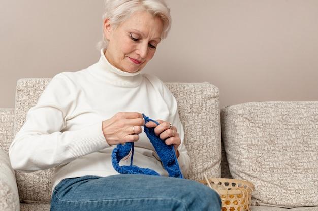 Low angle senior female knitting