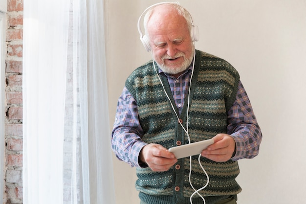 Low angle senior playing music on phone