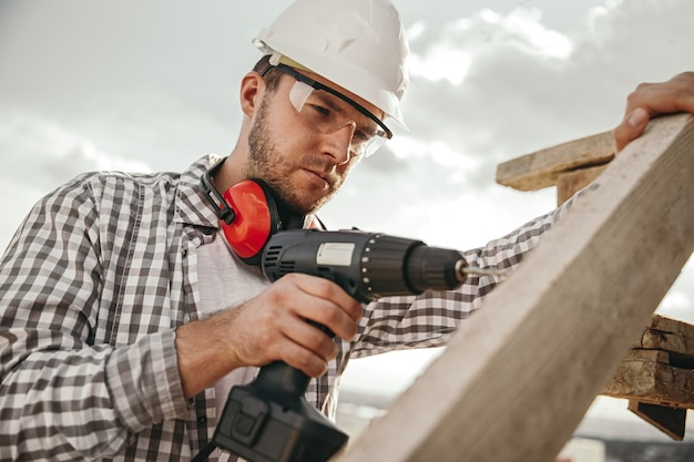 Low angle of serious bearded male worker in checkered shirt and protective glasses and hardhat drilling wooden structure, with professional instrument while working on construction site