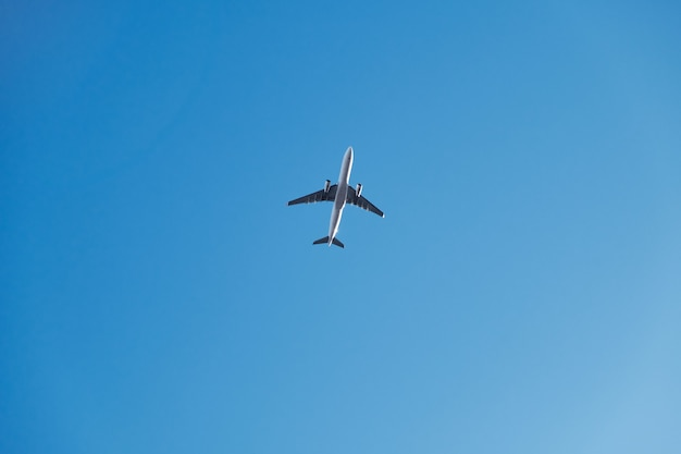 A low angle shot of an airplane flying under a blue sky and sunlight