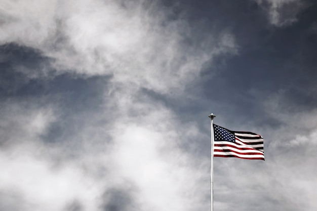 Low angle shot of the american flag on a pole under the cloudy sky