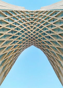 Low angle shot of the arc of azadi tower in tehran with blue sky