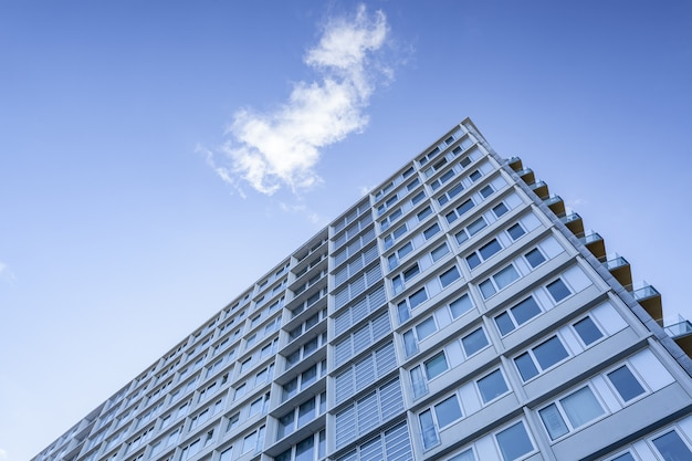 Colpo di angolo basso di un grande edificio sotto una nuvola nel bel cielo blu