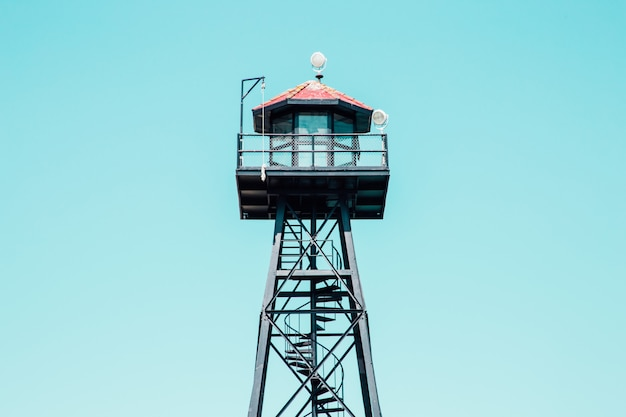 Low angle shot of a black lifeguard tower with red rooftop