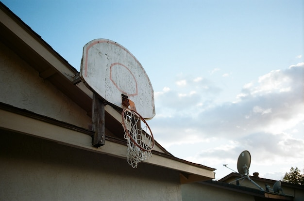 Low angle shot of a broken basketball basket on the top of a house