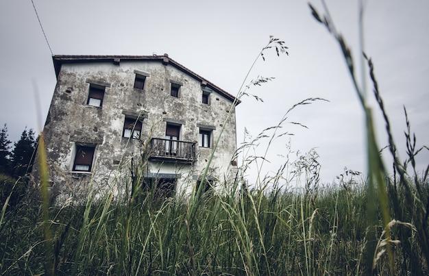 Inquadratura dal basso di un edificio nel mezzo di un campo erboso verde