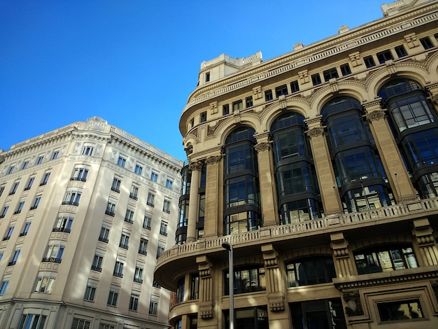 Low angle shot of buildings in spain under a clear blue sky