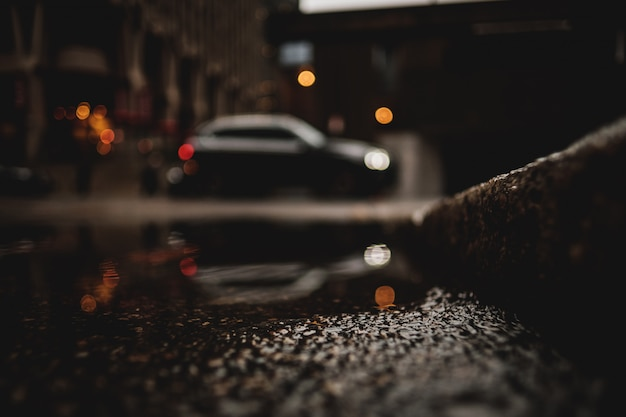 A low angle shot of a car with reflection in the puddle of water